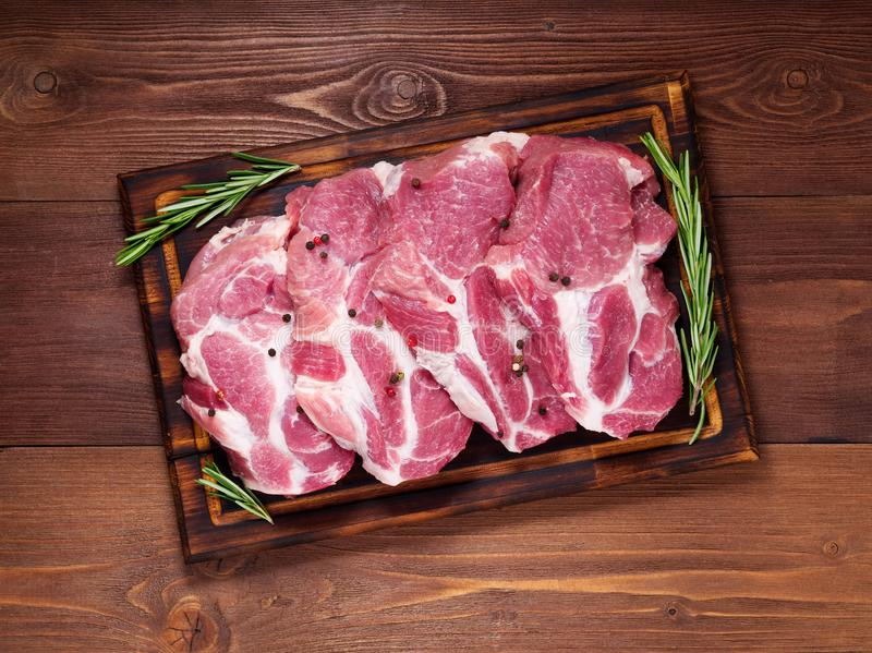 Raw Pork Loin chops on a cutting board with herbs rosemary on dark wooden background, top view royalty free stock images