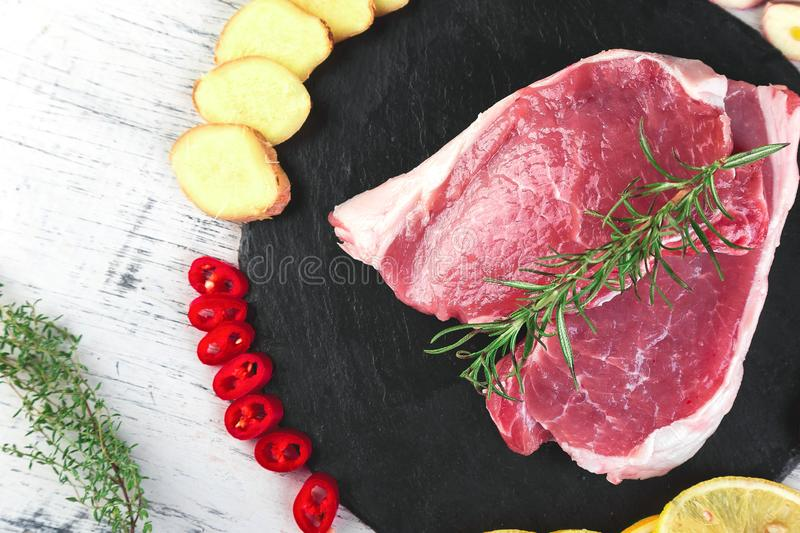 Raw pork meat on black slate plate with spice ingredient. Rosemary, ginger, chilli pepper, onion.Top view. Flat lay. Copy space royalty free stock images