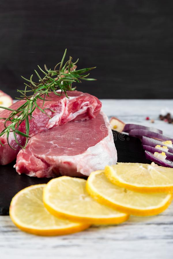 Raw pork meat on black slate plate with spice ingredient. Raw pork meat Tenderloin on black slate plate with spice ingredient - rosemary, ginger, chilli pepper stock photo
