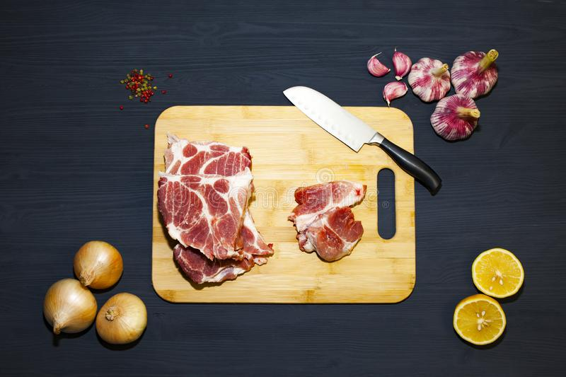 Raw pork meat on a black wooden surface and ingredients for cooking. Food background with copy space. Universal chef`s knife stock image