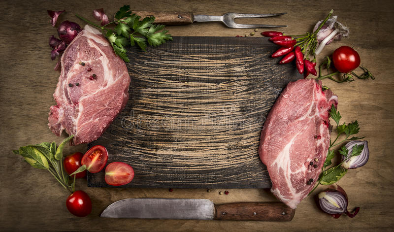 Raw pork meat chops with kitchen tools, fresh seasoning and ingredients for cooking rustic wooden background, top view, frame. stock photos