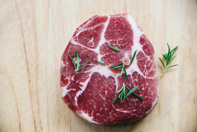 Raw pork meat / Fresh steak ready for grill with spices rosemary on wooden cutting board background stock photography