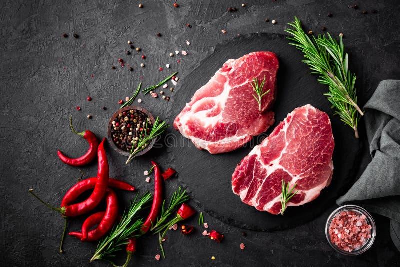 Raw pork meat. Fresh steaks on slate board on black background stock images