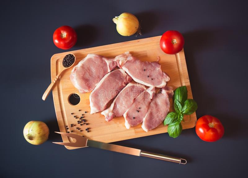 Raw pork meat steaks with fresh vegetables on cutting board on dark background. Top view royalty free stock photos