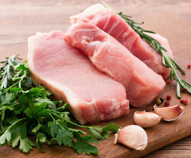 Raw pork meat on wooden desk. Raw pork meat with spices and vegetables on wooden table stock photo