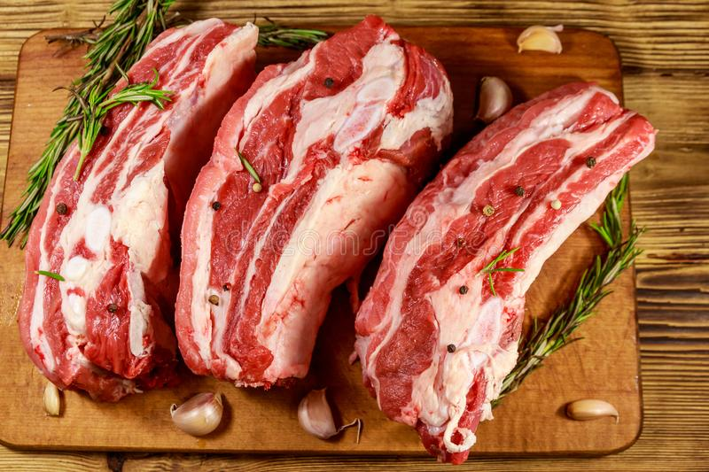 Raw pork ribs with spices, garlic and rosemary on wooden table. Top view stock photos