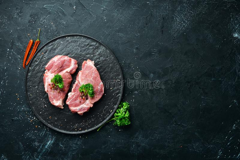 Raw pork steak. Fresh meat. On a plate of spices and herbs. Top view. Free space for your text royalty free stock photography