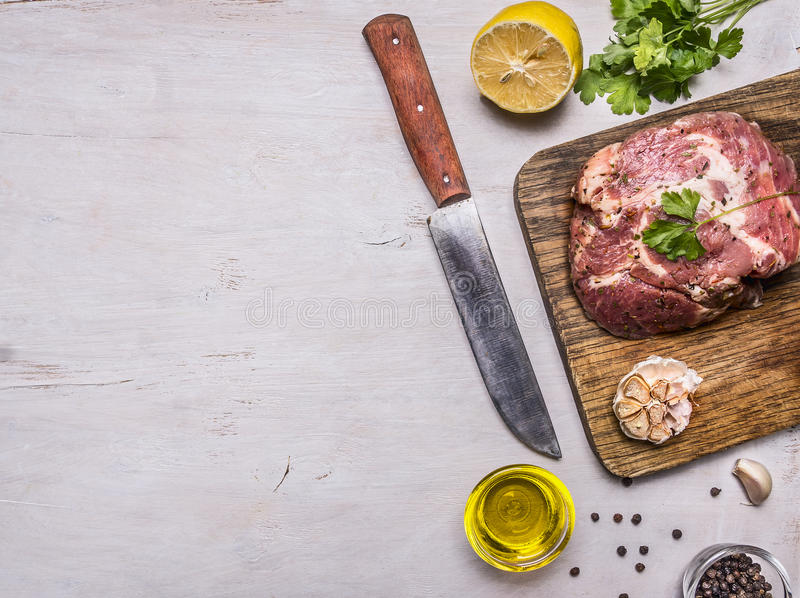 Raw pork steak with spices, garlic and herbs, lemon and butter knife for meat, border, place for text on wooden rustic background. Raw pork steak spices, garlic stock photography