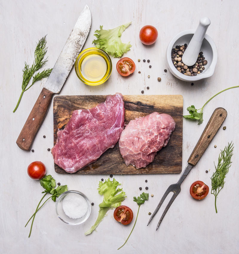 Raw Pork steak with vegetables and herbs, meat knife and fork, on a cutting board wooden rustic background top view close up. Raw Pork steak with vegetables and stock photo