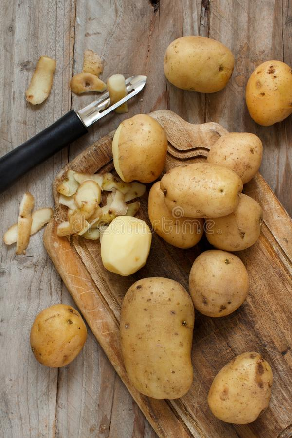 Raw potatoes with a vegetable peeler royalty free stock photos