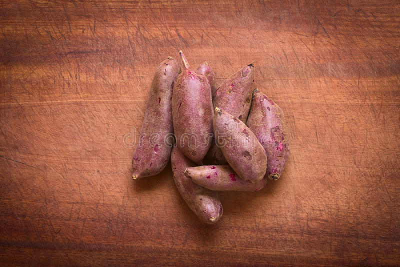 Raw Purple Sweet Potato. Overhead shot of raw purple sweet potato (lat. Ipomoea batatas) on wooden board photographed with natural light royalty free stock photography