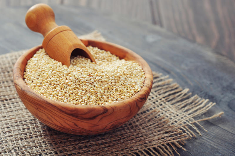 Raw quinoa seeds. In the wooden bowl on wooden background closeup stock photo