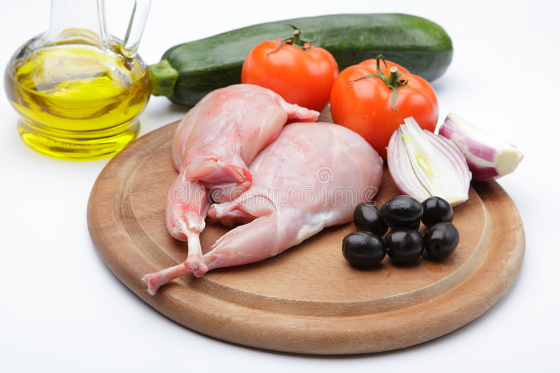 Raw rabbit legs with vegetables stock image