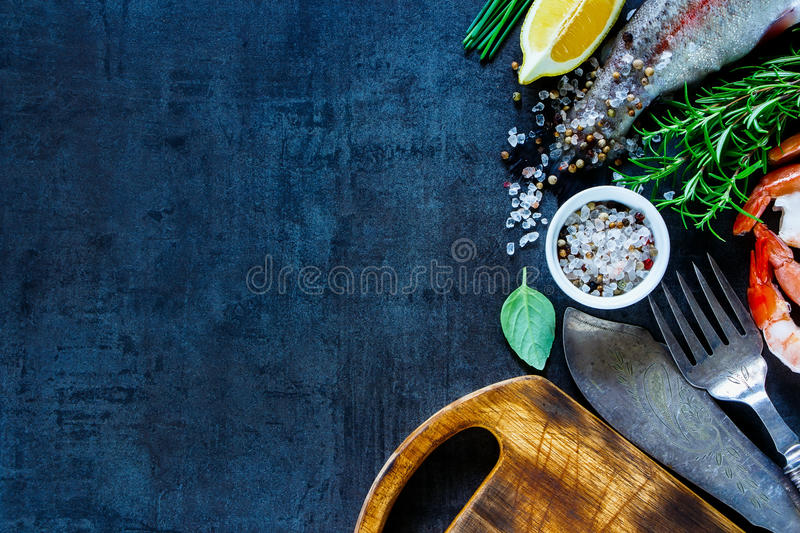 Raw rainbow trout. Top view of raw rainbow trout and shrimps on black slate stone board, preparation, copy space. Seafood with lemon, spices and herbs. Healthy royalty free stock photography