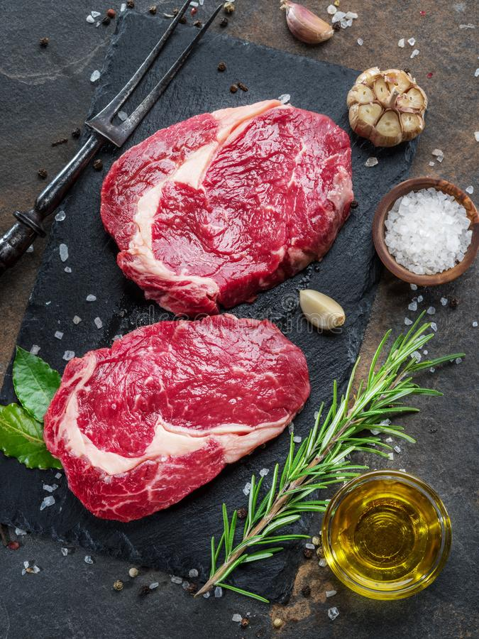 Raw Rib eye steak or beef steak on the graphite board with herbs and spices royalty free stock photos
