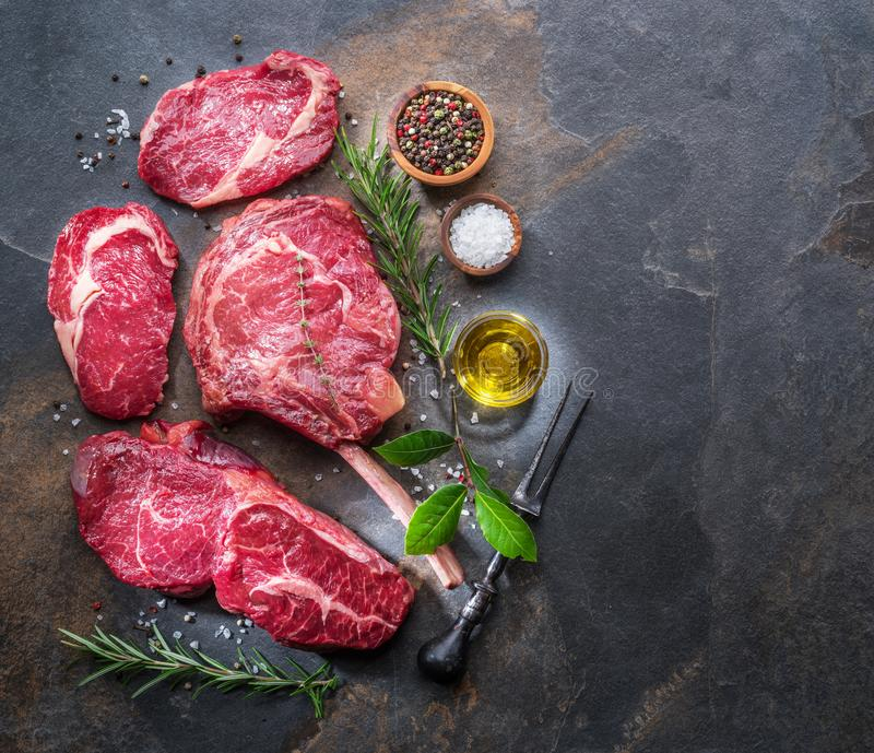 Raw Rib eye steak or beef steak on the graphite board with herbs and spices stock image