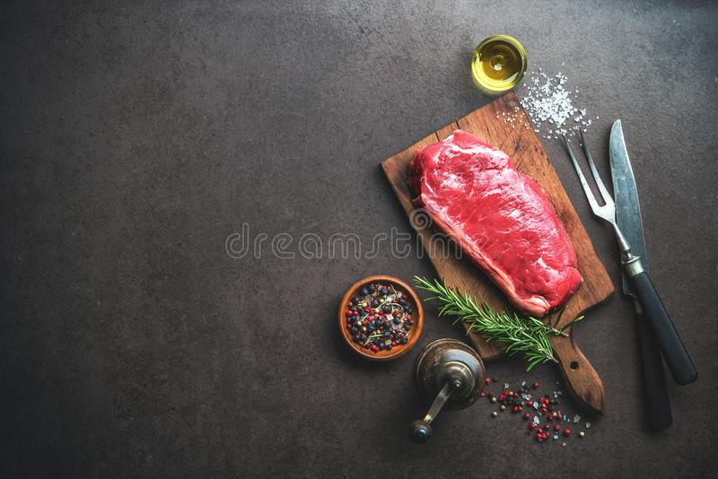 Raw ribeye beef steak with herbs and spices. On cutting board. Top view royalty free stock photo