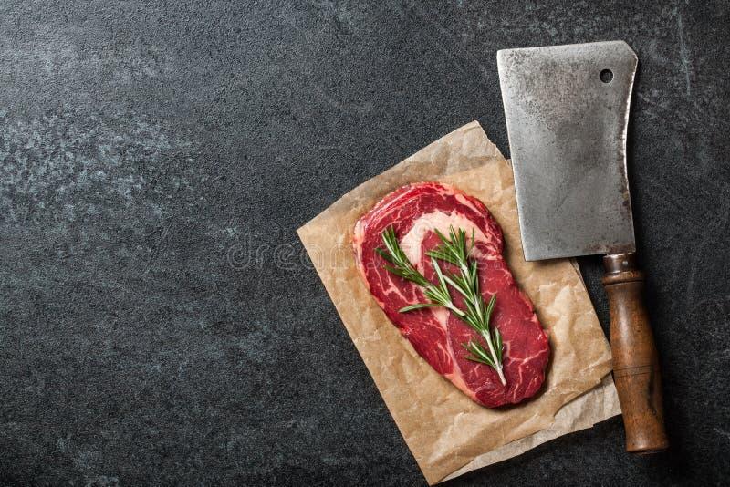 Raw ribeye steak and butcher knife on blackboard. Copy space royalty free stock image