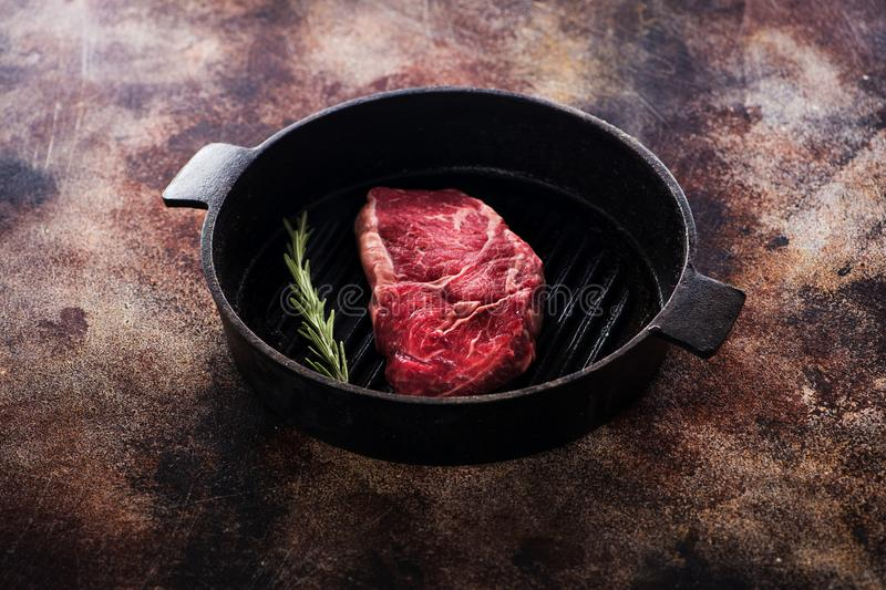 Raw ribeye steak on a cast-iron pan. With rosemary stock image