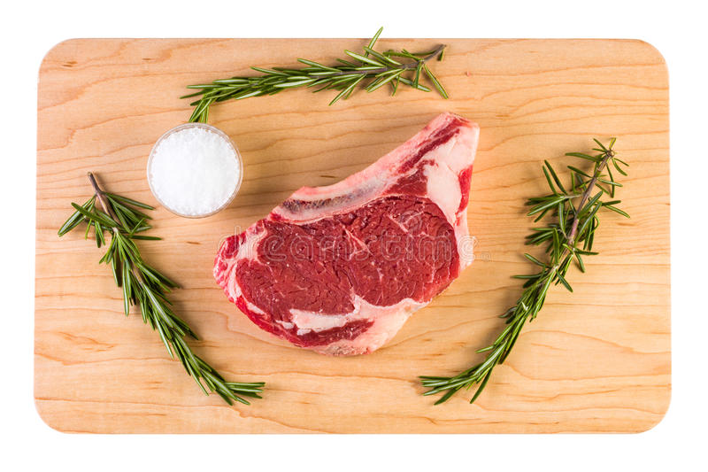 Raw Ribeye Steak. Close up view of a raw beef ribeye steak on a wood board with course sea salt and rosemary royalty free stock images