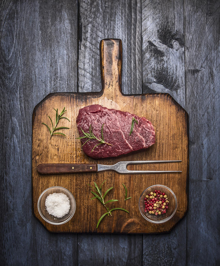 Raw ribeye steak on a cutting board with a fork, with rosemary salt and pepper on rustic wooden background, top view royalty free stock photos