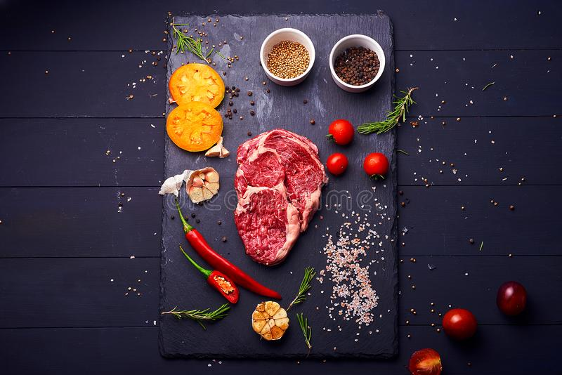 Raw Ribeye steaks or beef steak on graphite tray with herbs. Top view. Raw pork steaks with seasoning on stone plate. Gray slate background royalty free stock photo