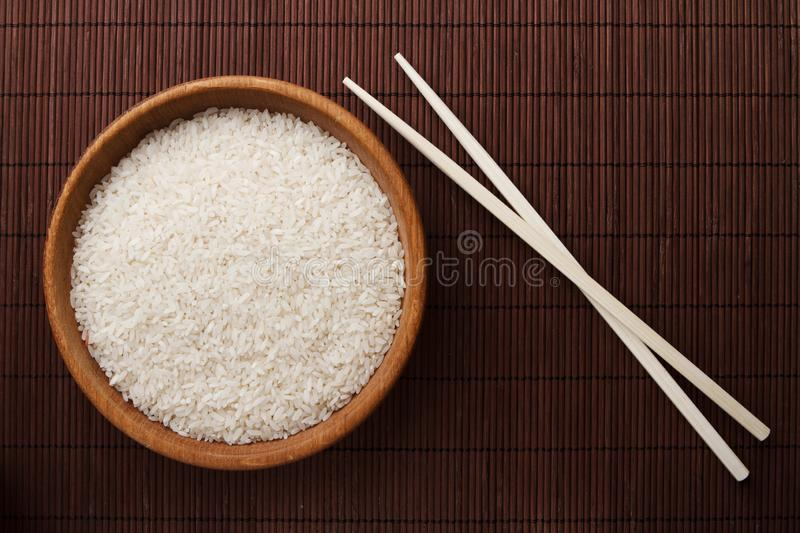Raw rice in wooden bowl stock photography