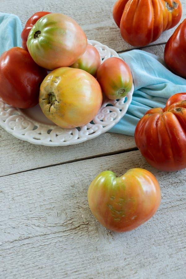 Raw ripe graden tomatoes on wooden background. Vegetarian ingredients. Seasonal produce stock photo