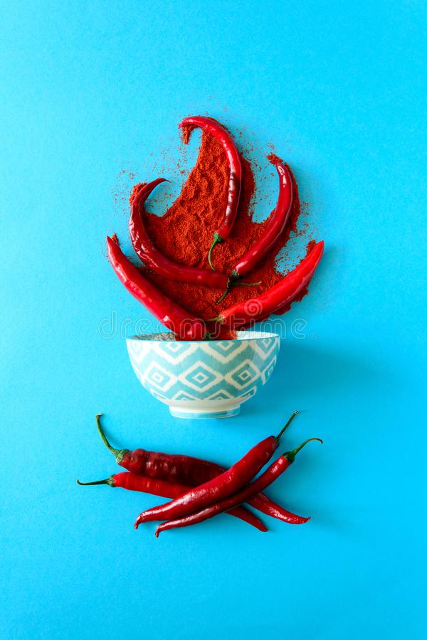 Raw ripe red chili pepper peas and chili powder in bonfire form lying on blue paper background. Top view. Flat lay.  stock image