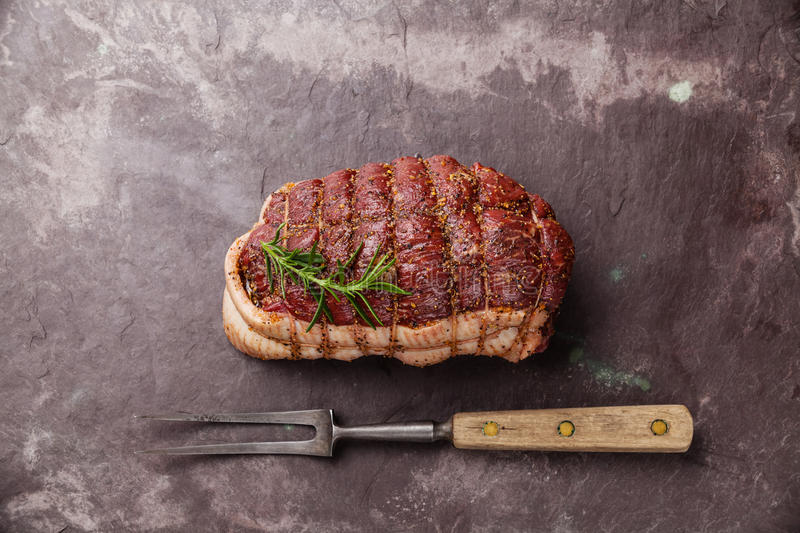 Raw roast beef Rump. And meat fork on dark stone slate background stock image