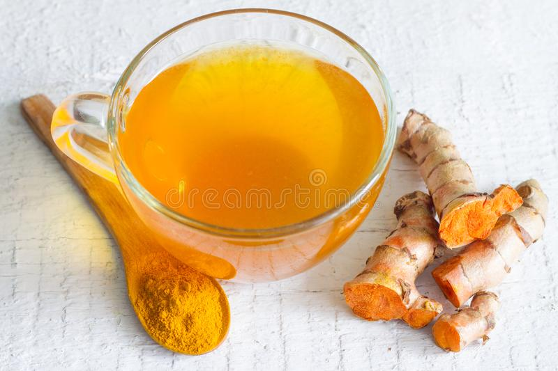 Raw roots of tumeric and tea on white planks detox concept royalty free stock photos