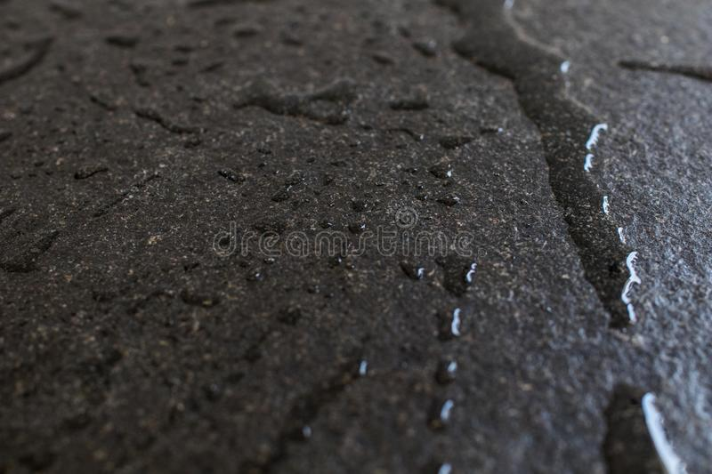 Raw and rough black granite slab wet with water. Drops and patch stock photos