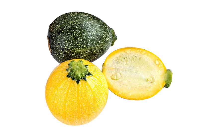 Raw round yellow and green zucchini and a cut one isolated on white. royalty free stock photos