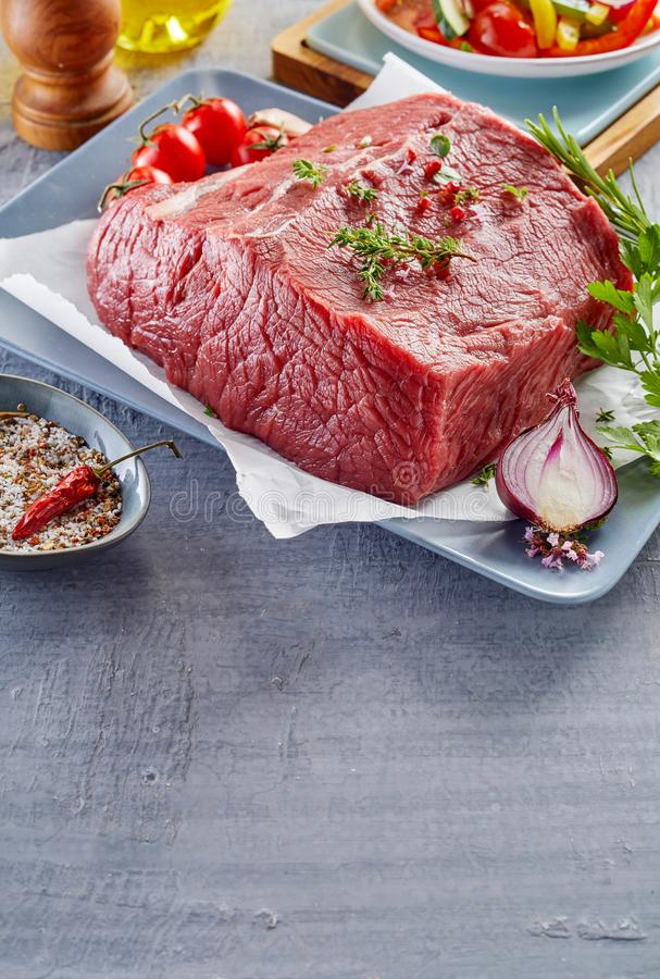Raw rump steak prepared on plate. Raw rump steak with spices and vegetables prepared on plate stock images