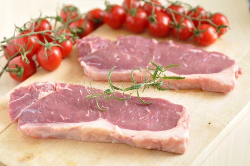 Raw rump steak. On a wooden table stock photos