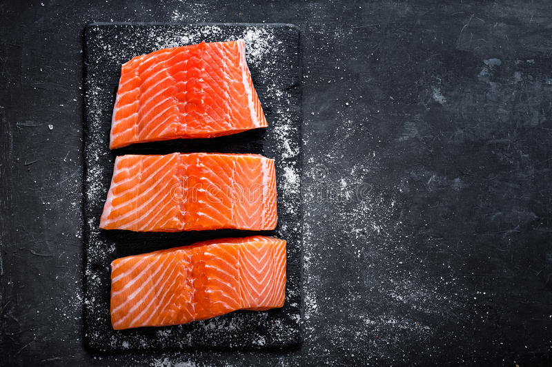 Raw salmon filet on dark slate background, wild atlantic fish, space for text. Raw salmon filet on dark slate background, wild atlantic fish, top view royalty free stock images