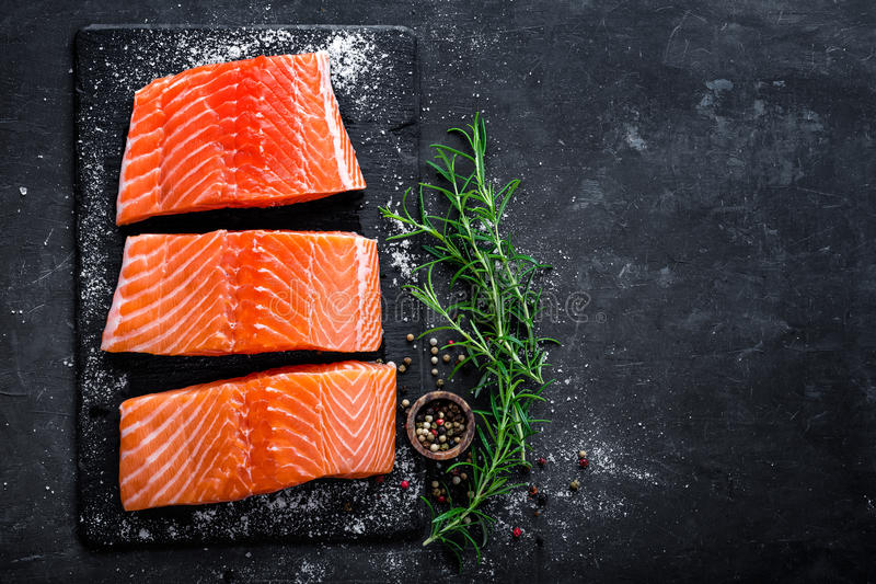 Raw salmon filet on dark slate background, wild atlantic fish, space for text royalty free stock photo