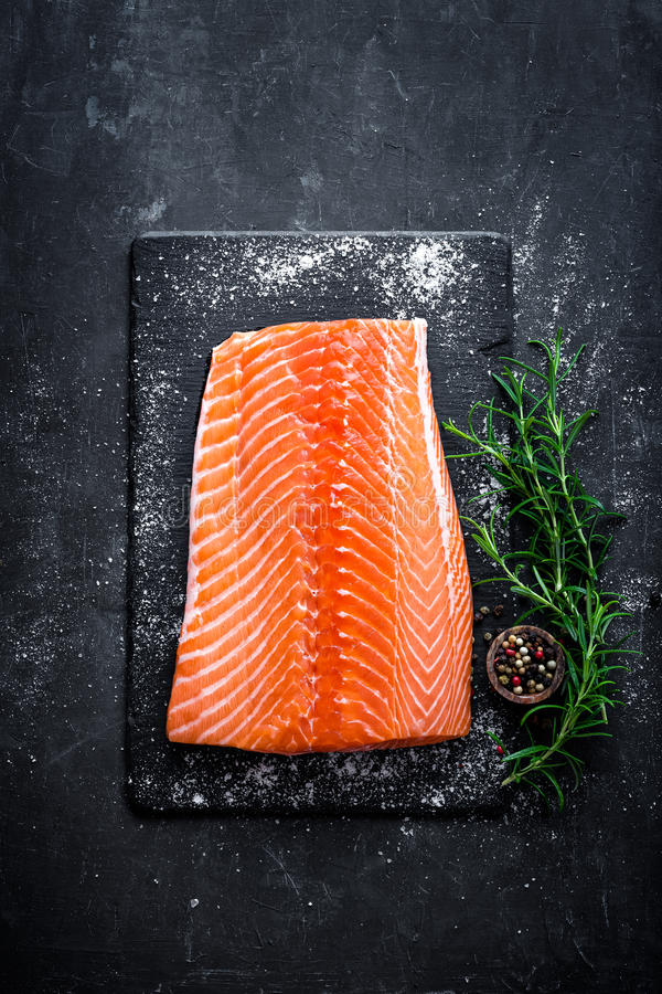 Raw salmon filet on dark slate background, wild atlantic fish, space for text. Raw salmon filet on dark slate background, wild atlantic fish, top view royalty free stock photography