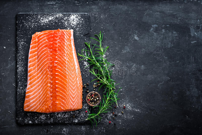 Raw salmon filet on dark slate background, wild atlantic fish, space for text. Raw salmon filet on dark slate background, wild atlantic fish, top view stock photography