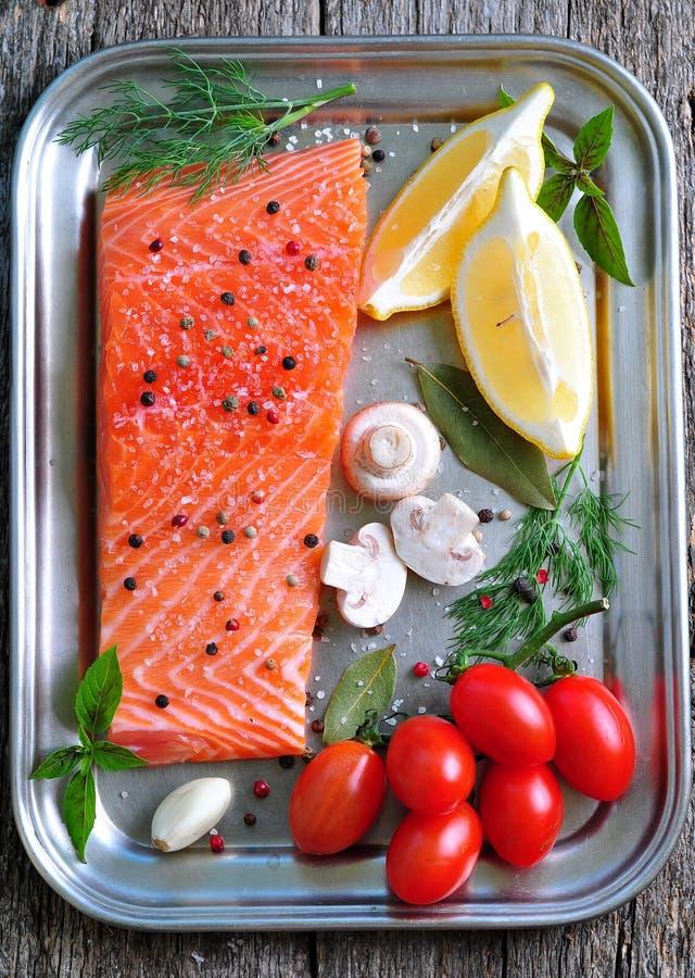 Raw salmon fillet with cherry tomato, mushroom, dill, garlic, lemon and sea salt. Dinner stock photos