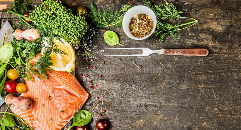Raw salmon fillet with fresh seasoning, spices and fork on rustic wooden background, top view, banner for website. With cooking concept stock image