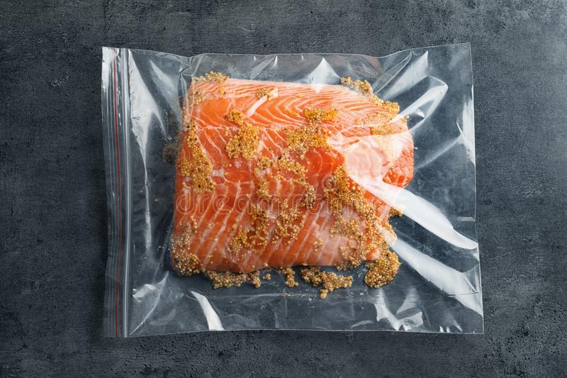 Raw salmon fillet with marinade in plastic bag. On grey background, top view stock photos
