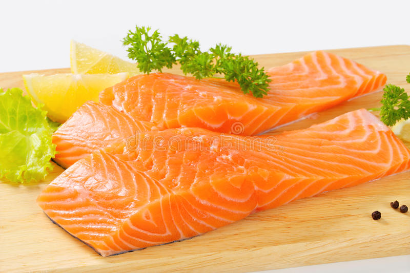 Raw salmon fillets. On cutting board stock photography