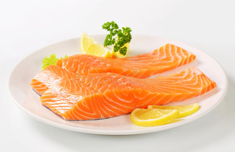 Raw salmon fillets. And lemon on plate stock photo