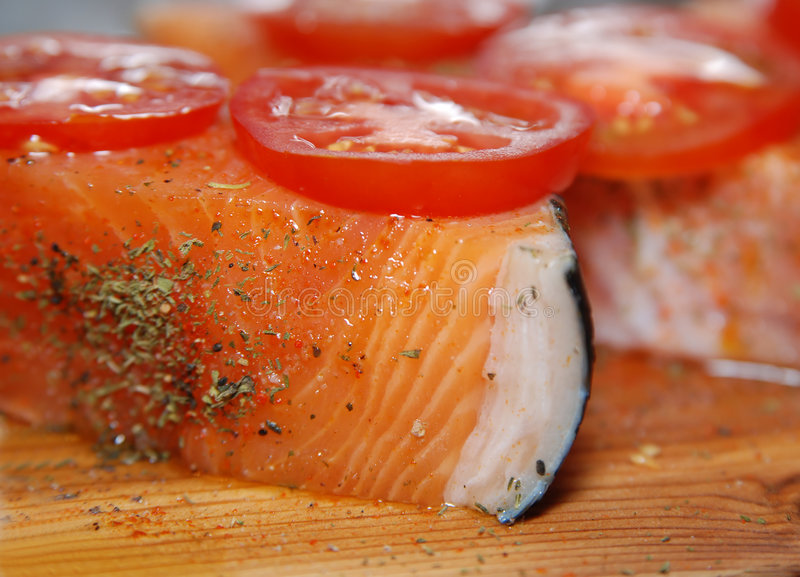 Raw Salmon fillets. A raw Salmon fillets with tomatoes, ready to grill. Close up stock images
