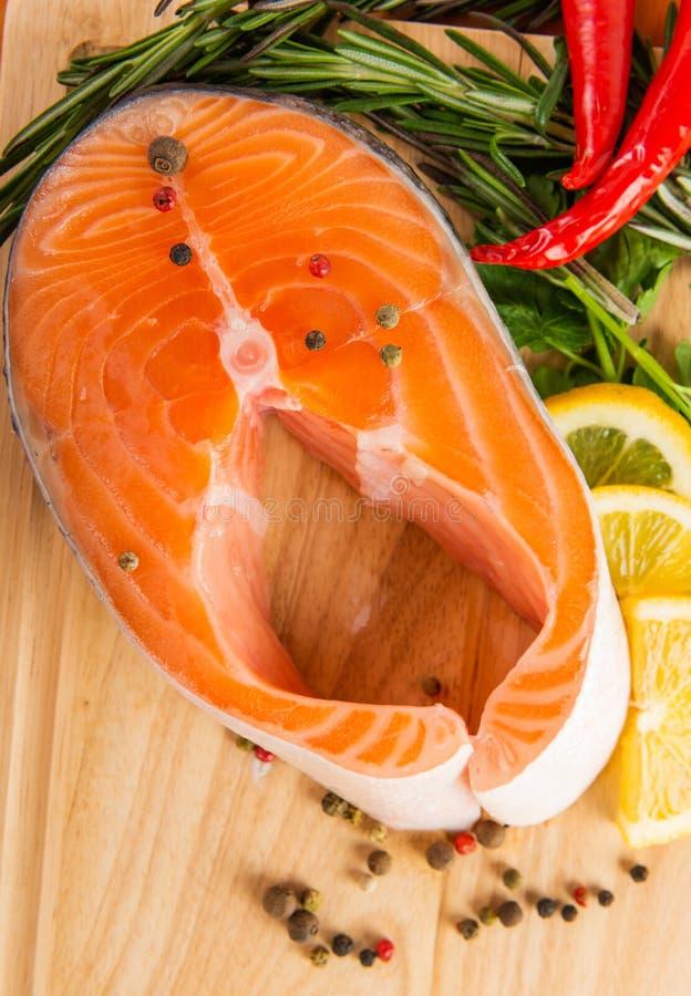 Raw salmon fillets. Pepper, salt, lemon and rosemary royalty free stock photo