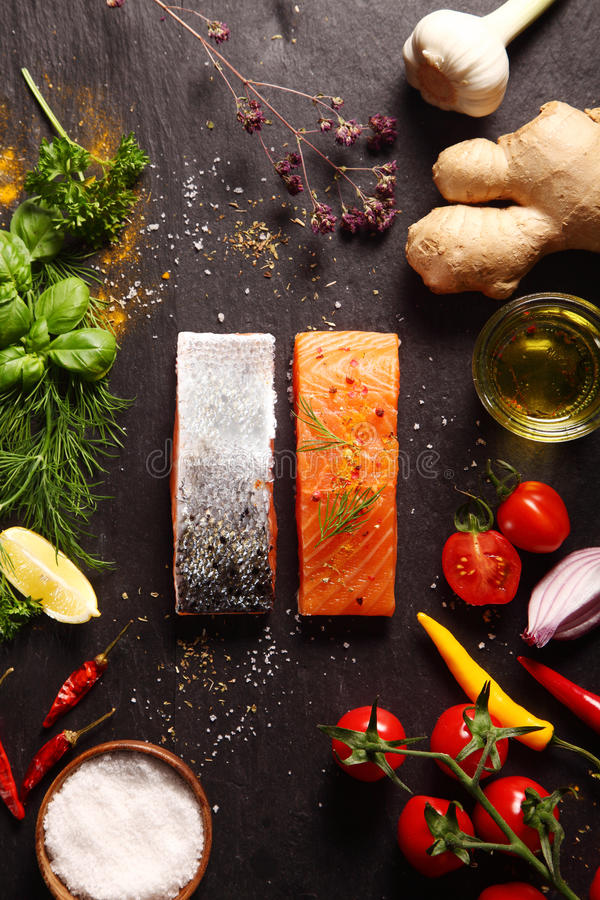 Raw salmon fillets with savory ingredients. Raw salmon fillets surrounded by savory ingredients including spicy root ginger, fresh herbs, tomato, chili pepper stock photography