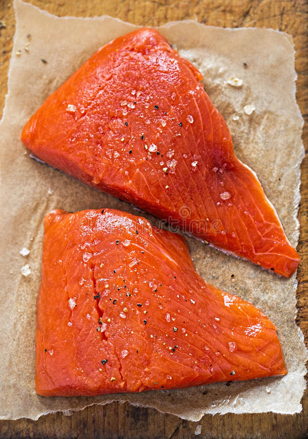 Raw salmon fillets seasoned. Raw salmon fillets with salt and pepper royalty free stock image