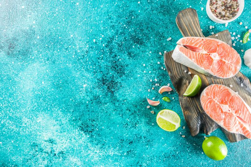 Raw salmon fish steaks with spices. On marine blue concrete stone background copy space royalty free stock image