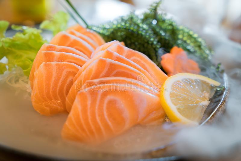 Raw salmon slice or salmon sashimi in Japanese style fresh serve. On ice in bowl stock image